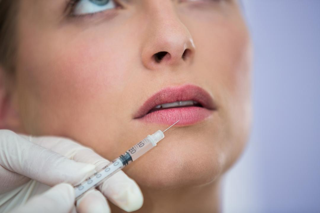 Close-up of female patient receiving a botox injection on lips