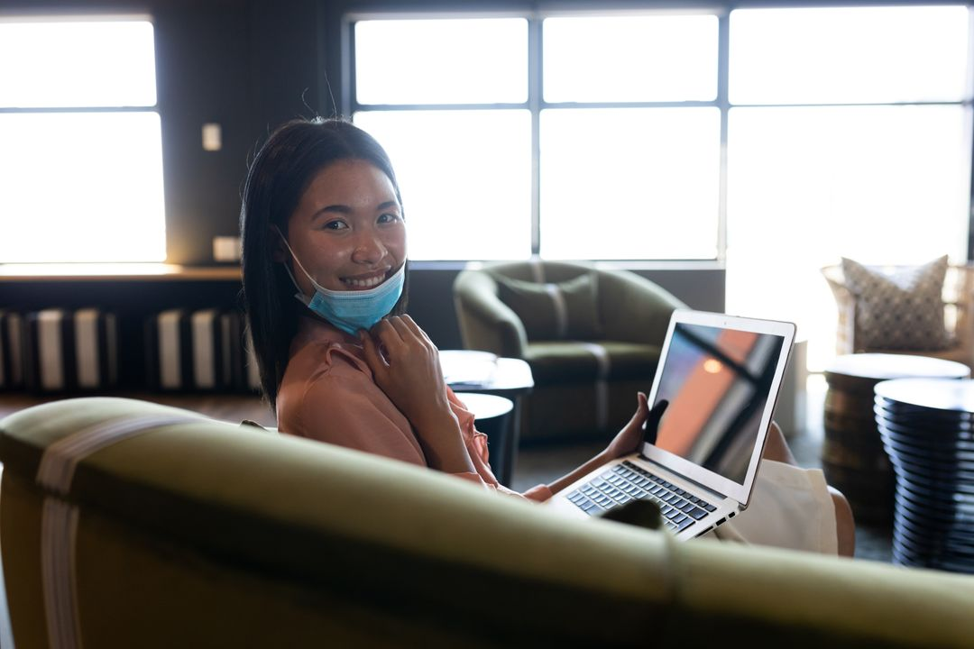 Asian woman wearing a face mask sitting on couch using laptop looking at camera smiling. Health and hygiene in creative office during coronavirus covid 19 pandemic. Free Stock Images from PikWizard