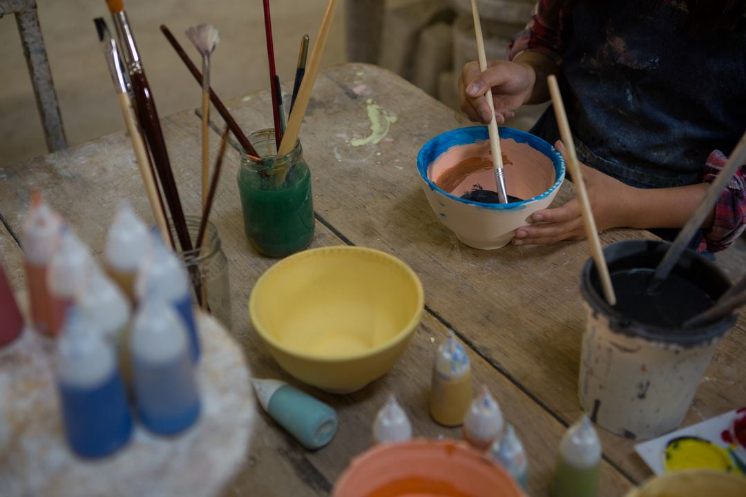Mid section of girl painting a bowl in pottery workshop Free Stock Images from PikWizard