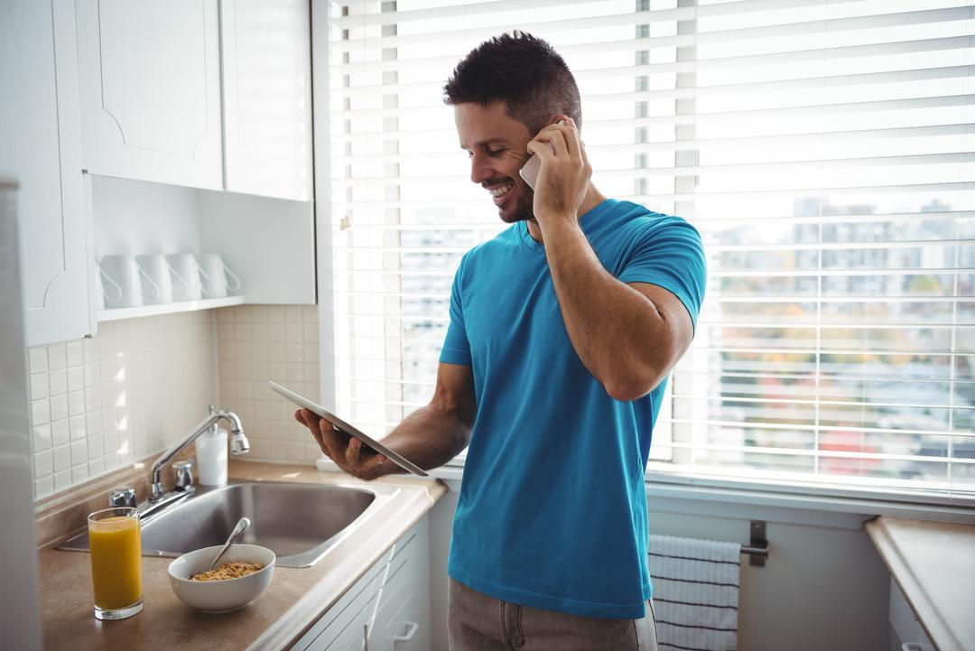 Man talking on mobile phone while using digital tablet in kitchen at home