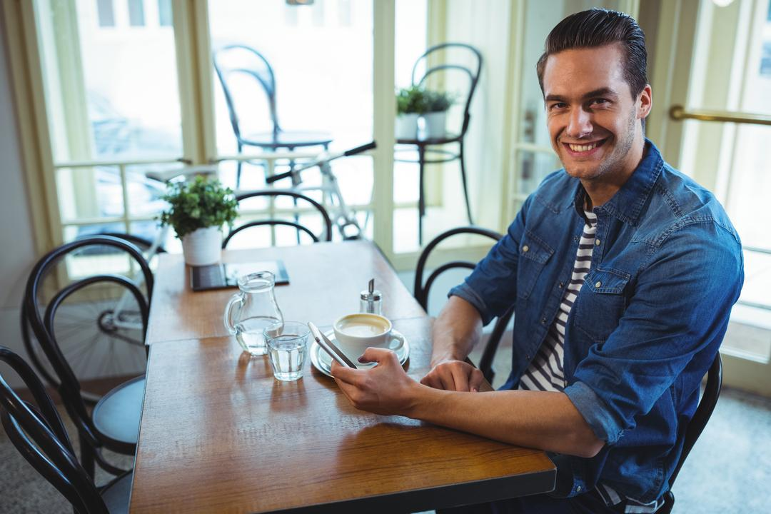 Portrait of smiling man using mobile phone in café