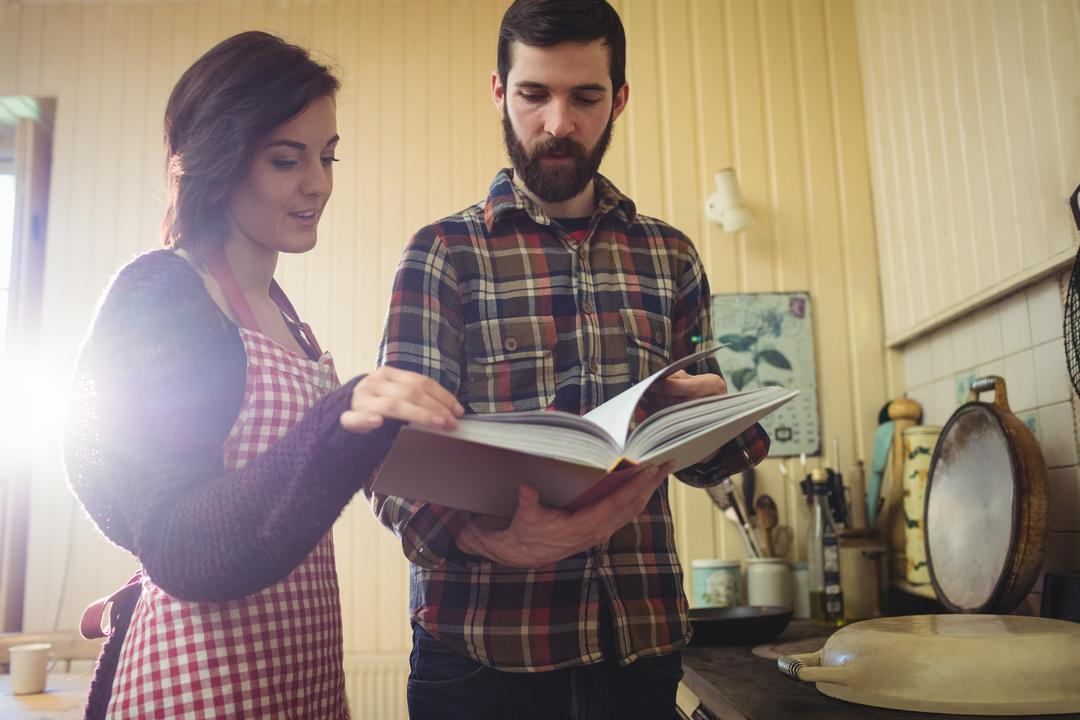 Couple looking at recipe book in kitchen at home