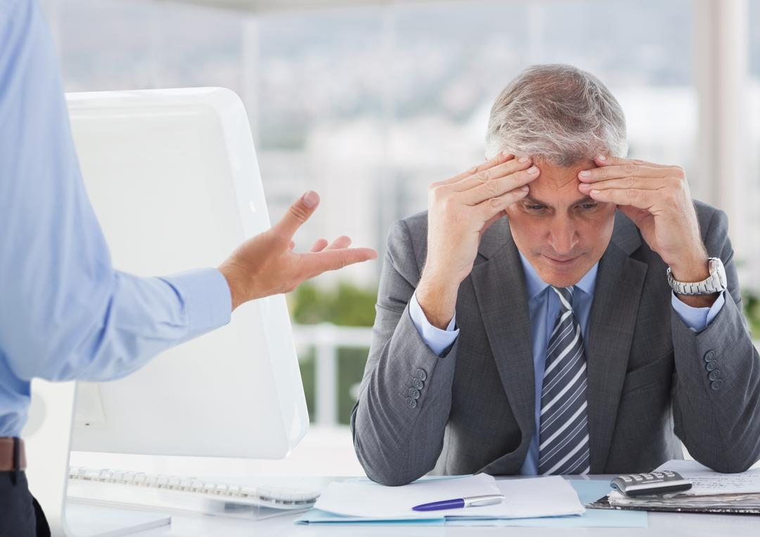 Frustrated businessman sitting with hands on forehead in office Free Stock Images from PikWizard