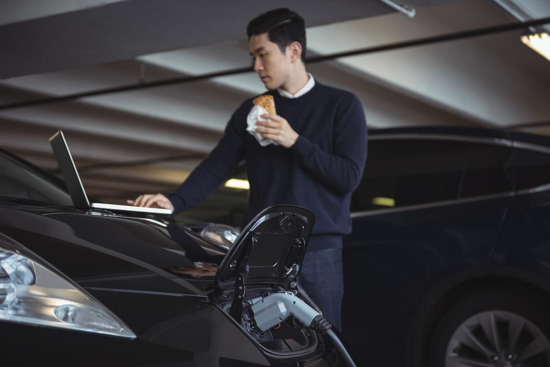 Man using laptop while charging electric car in garage Free Stock Images from PikWizard