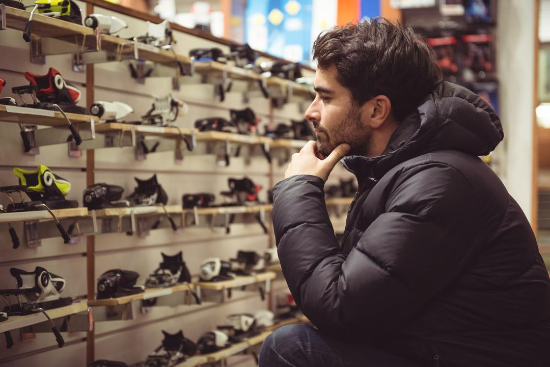 Handsome man selecting ski binding in a shop Free Stock Images from PikWizard