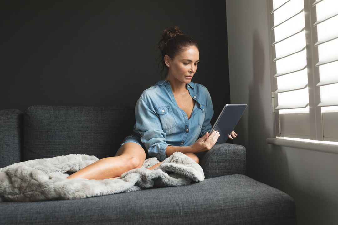 Front view of woman using digital tablet while sitting on sofa in a comfortable home