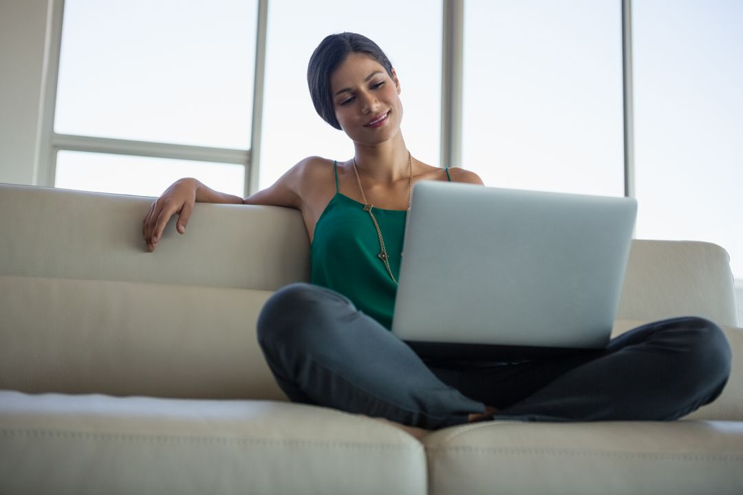 Beautiful businesswoman using laptop while sitting on sofa at office Free Stock Images from PikWizard