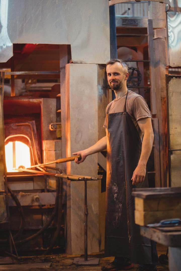 Portrait of glassblower heating glass in glassblowers oven at glassblowing factory Free Stock Images from PikWizard