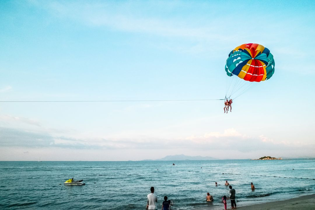 busy beach landscape with parachute in sky background