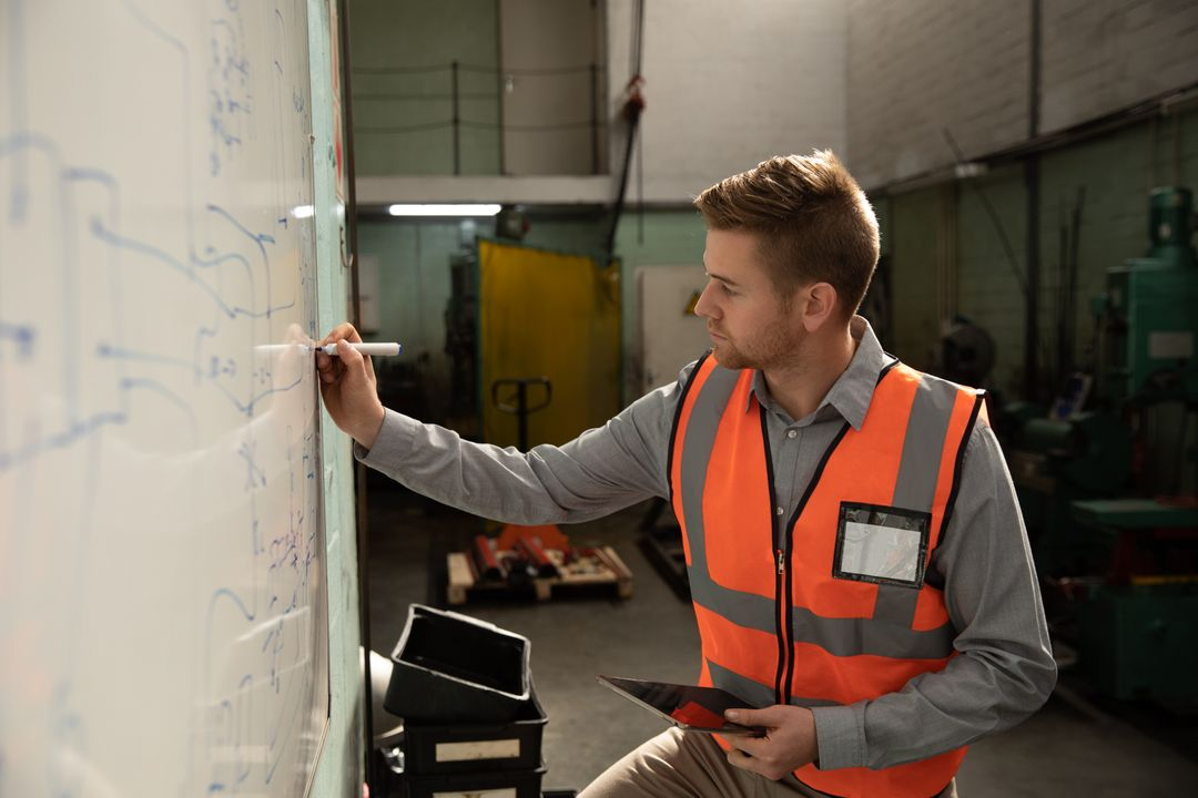Caucasian male factory worker wearing a high vis vest writing on whiteboard holding a digital tablet. Industrial worker at a factory making hydraulic equipment.