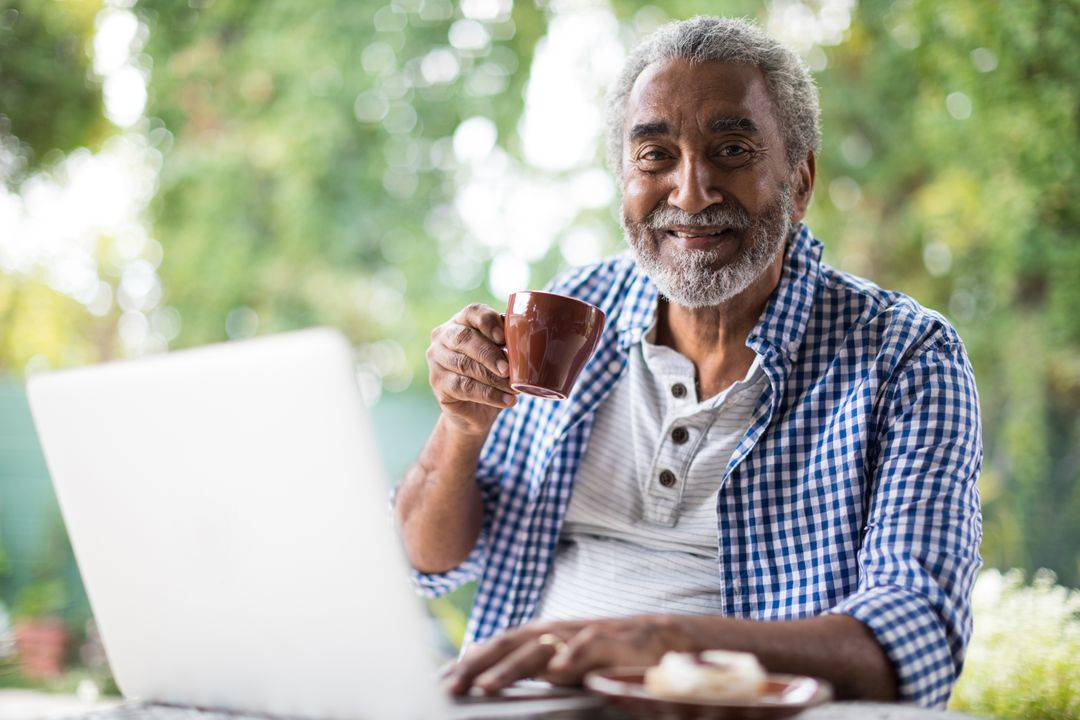 Portrait of senior man having coffee while using laptop at table in yard