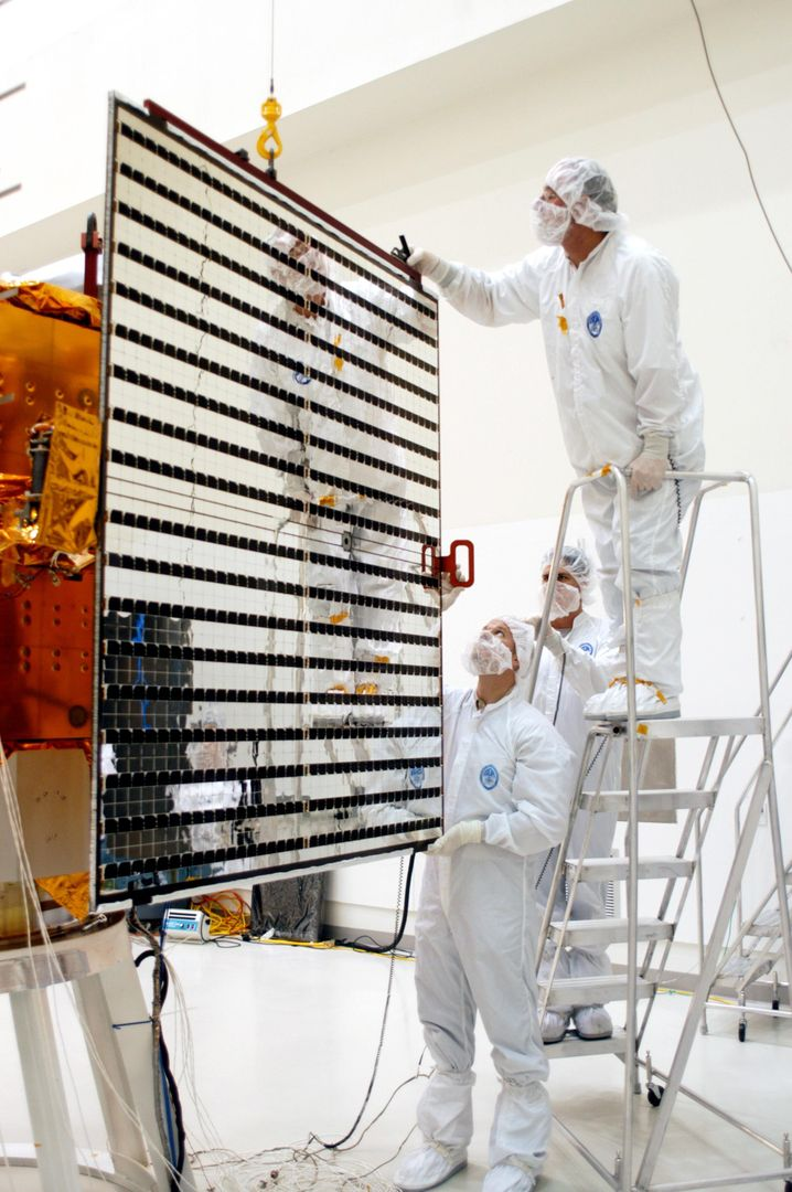 KENNEDY SPACE CENTER, FLA.  - Technicians at Astrotech in Titusville, Fla., guide a solar panel closer to NASA's MESSENGER spacecraft for installation.  It is one of two large solar panels, supplemented with a nickel-hydrogen battery, that will provide MESSENGER's power.  MESSENGER is scheduled to launch Aug. 2 aboard a Boeing Delta II rocket from Pad 17-B, Cape Canaveral Air Force Station, Fla. It will return to Earth for a gravity boost in July 2005, then fly past Venus twice, in October 2006 and June 2007. The spacecraft uses the tug of Venus' gravity to resize and rotate its trajectory closer to Mercury's orbit.  Three Mercury flybys, each followed about two months later by a course-correction maneuver, put MESSENGER in position to enter Mercury orbit in March 2011. During the flybys, MESSENGER will map nearly the entire planet in color, image most of the areas unseen by Mariner 10, and measure the composition of the surface, atmosphere and magnetosphere. It will be the first new data from Mercury in more than 30 years - and invaluable for planning MESSENGER's year-long orbital mission.  MESSENGER was built for NASA by the Johns Hopkins University Applied Physics Laboratory in Laurel, Md.