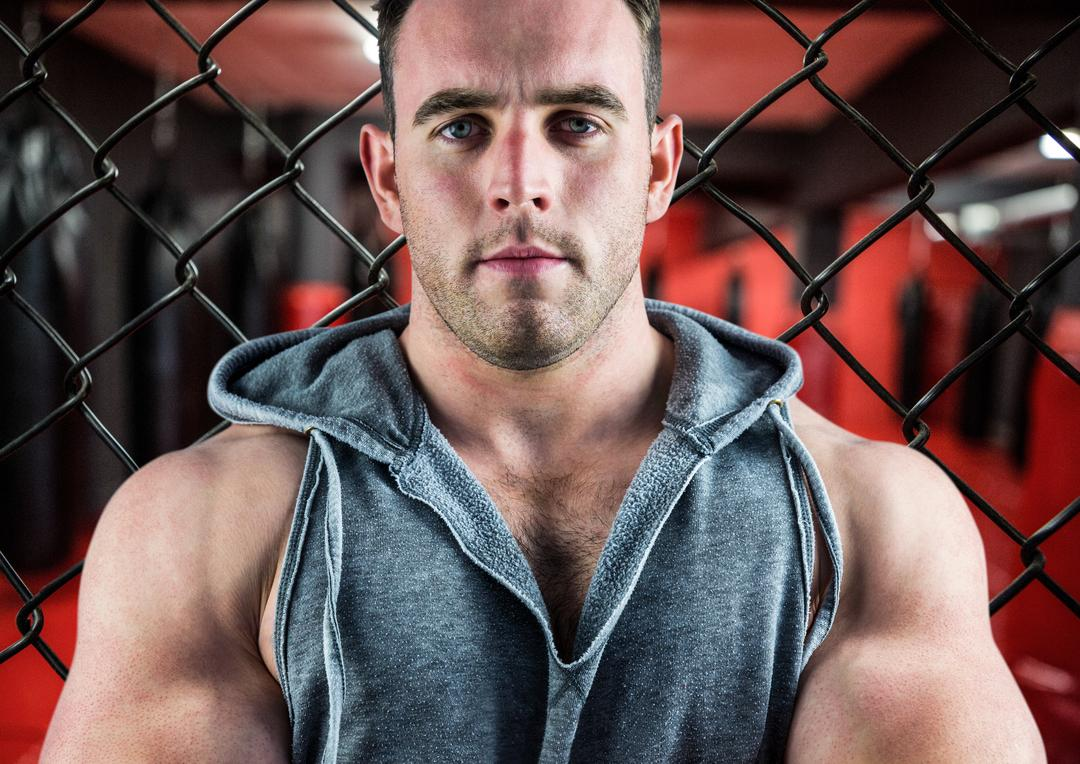 Smart muscular man standing against a fence in fitness studio Free Stock Images from PikWizard