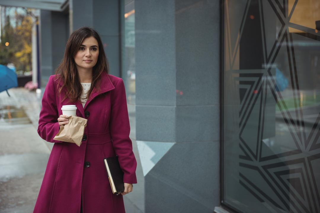Businesswoman holding disposable coffee cup, parcel and diary walking on sidewalk