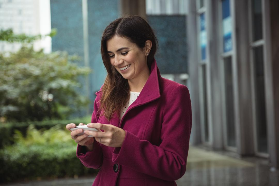 Smiling businesswoman using phone on street
