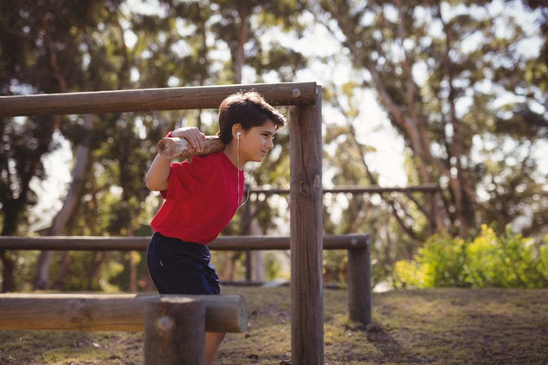 Happy boy exercising with log while listening music during obstacle course in boot camp Free Stock Images from PikWizard