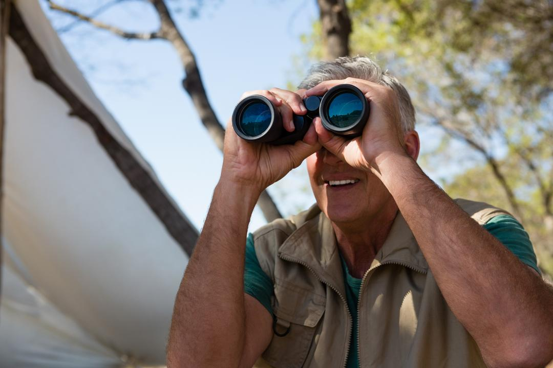 Mature man looking through binocular by tent