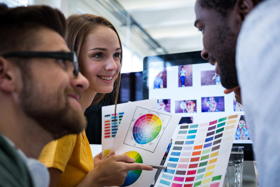 Group of graphic designers choosing color from color chart in office Free Stock Images from PikWizard