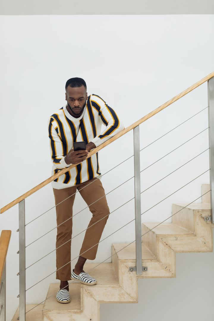 Digital composite of an African-American man using a smartphone while standing against the wooden rail of the stairs