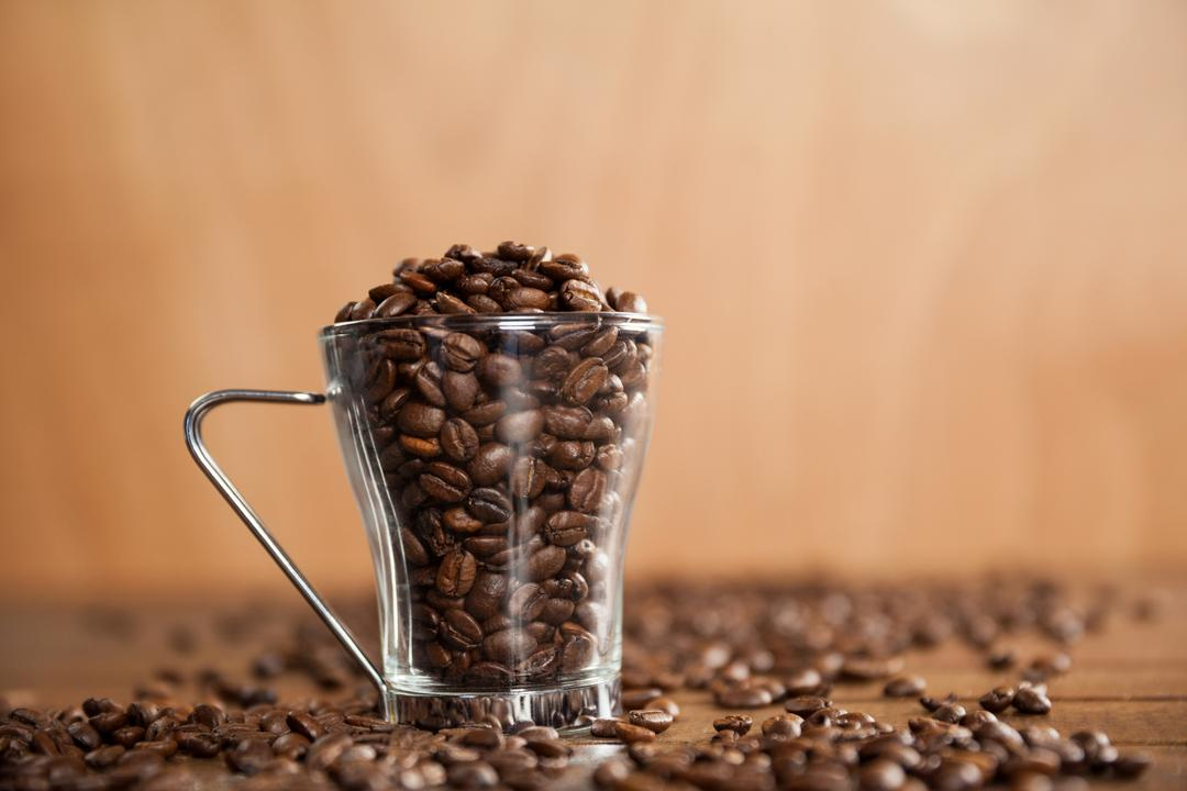 Transparent glass cup filled with coffee beans on wooden table Free Stock Images from PikWizard