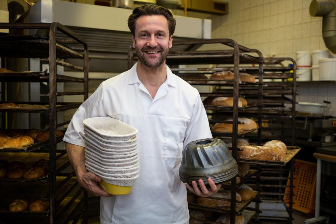 Portrait of smiling baker holding mould and stack of boxes in bakery kitchen