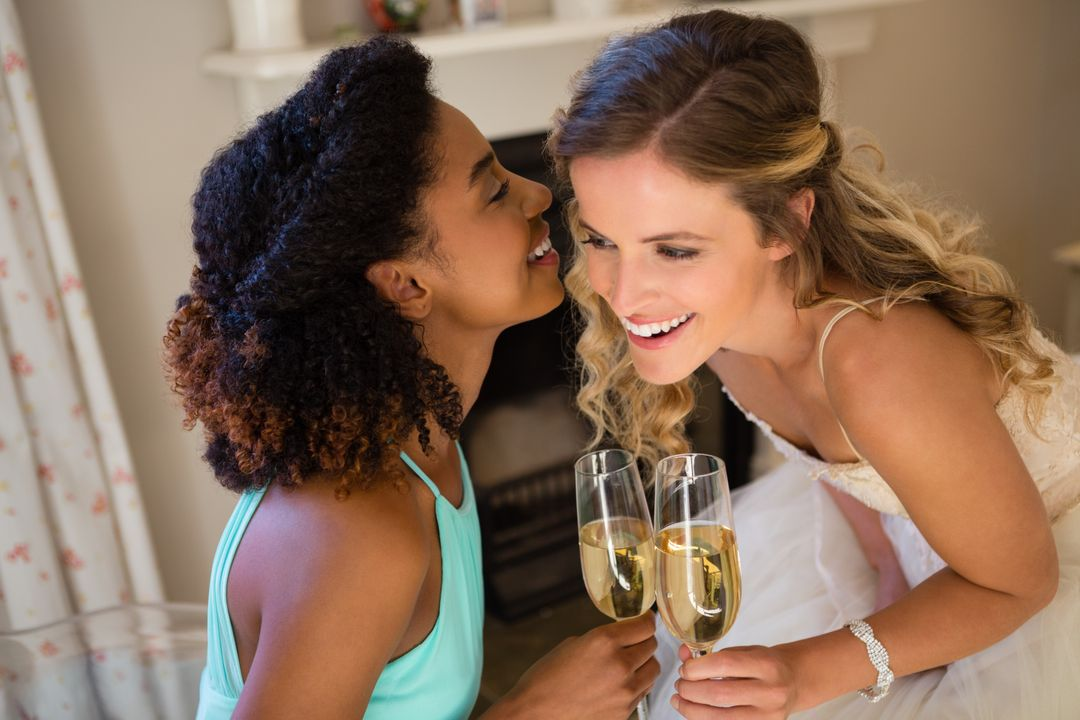 Bridesmaid whispering into bride ear while having champagne in bedroom Free Stock Images from PikWizard