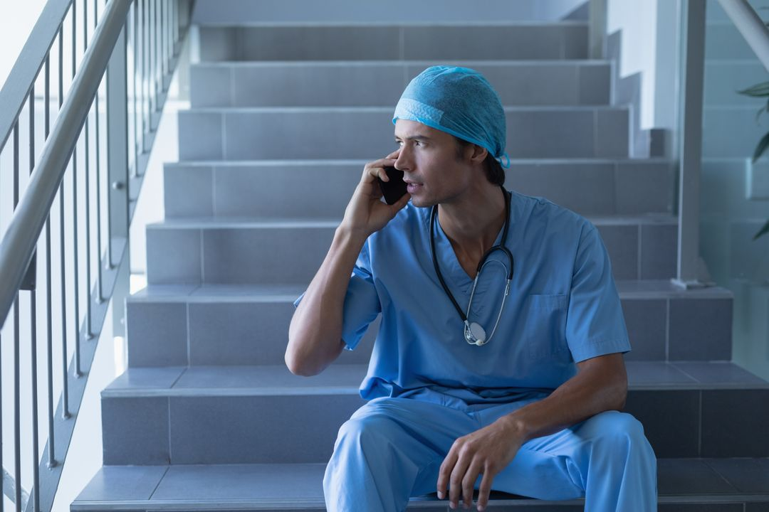 Male surgeon talking on mobile phone while sitting at stairs in hospital