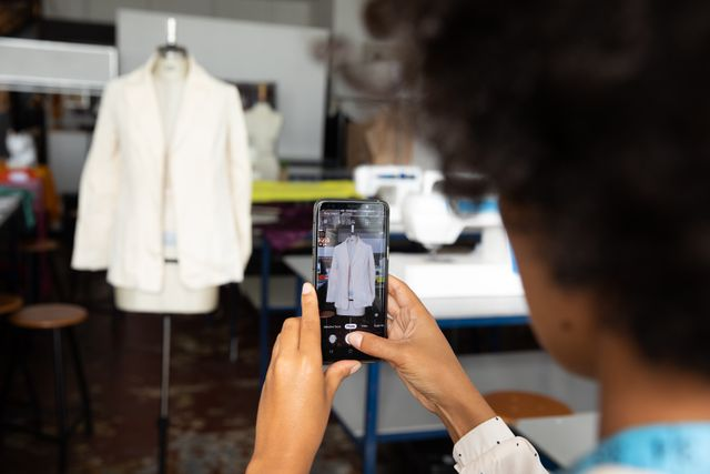 Rear view of a young mixed race female fashion student taking photo with a smartphone of a white jacket, in a studio at fashion college.