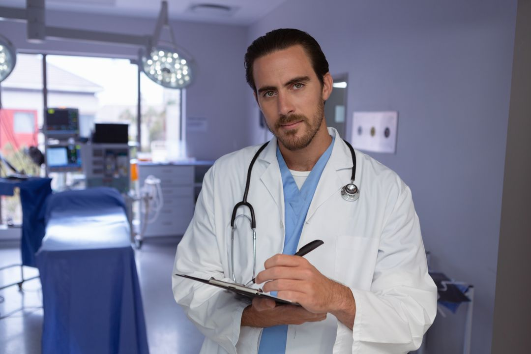 Front view of male doctor writing on clipboard in operation room at hospital Free Stock Images from PikWizard