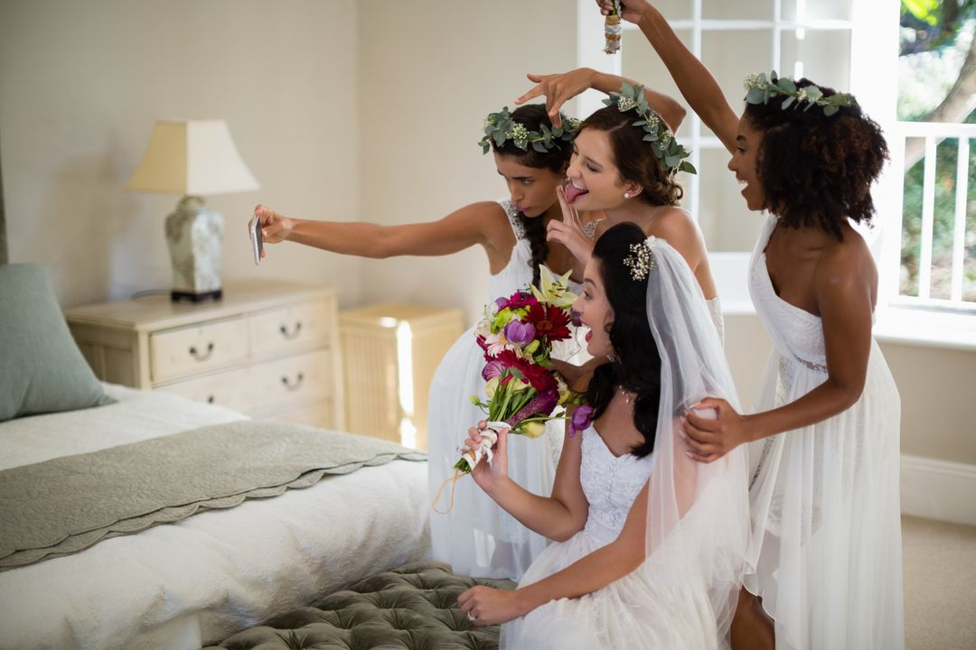 Smiling bride and bridesmaid taking selfie at home Free Stock Images from PikWizard