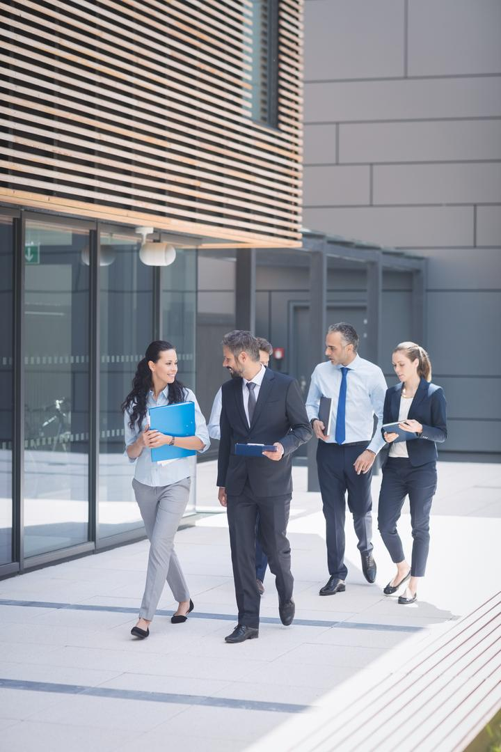 Group of confident business people walking outside office building