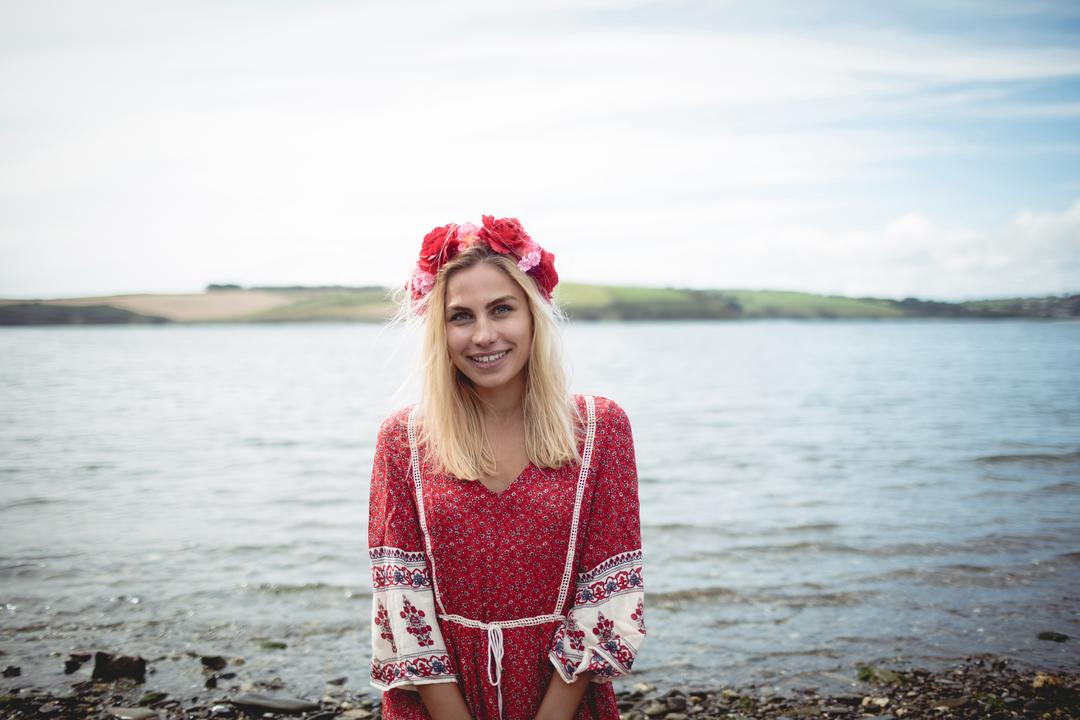Carefree blonde woman wearing a flower tiara sitting near a river