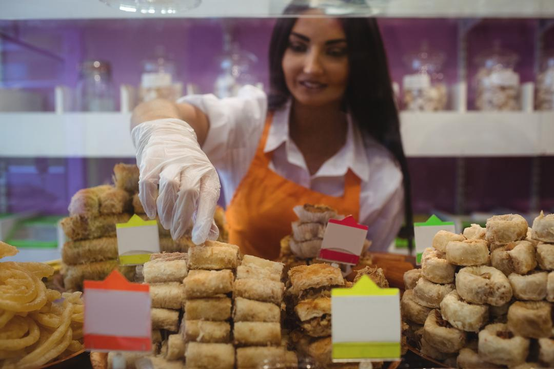Female shopkeeper arranging turkish sweets at counter in shop Free Stock Images from PikWizard