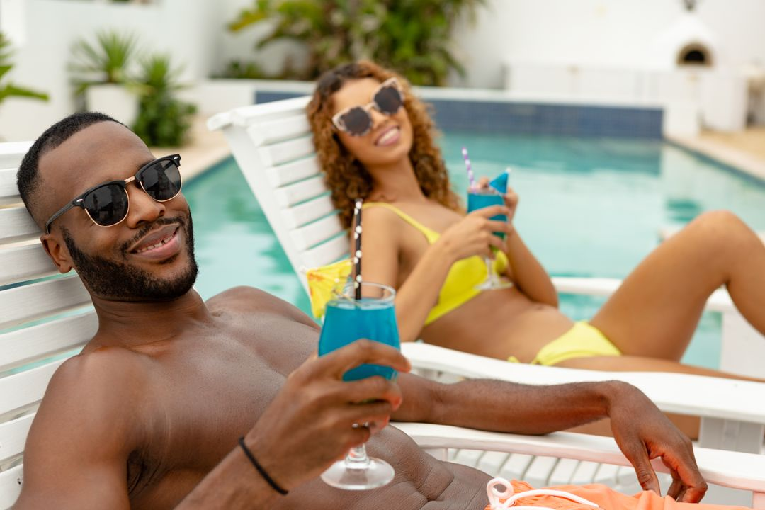 Front view of happy diverse couple having cocktail drink while relaxing on a sun lounger near swimming pool. Summer fun at home by the swimming pool