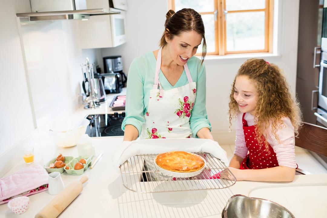 Mother interacting with daughter while holding pancake in cooling rack at kitchen
