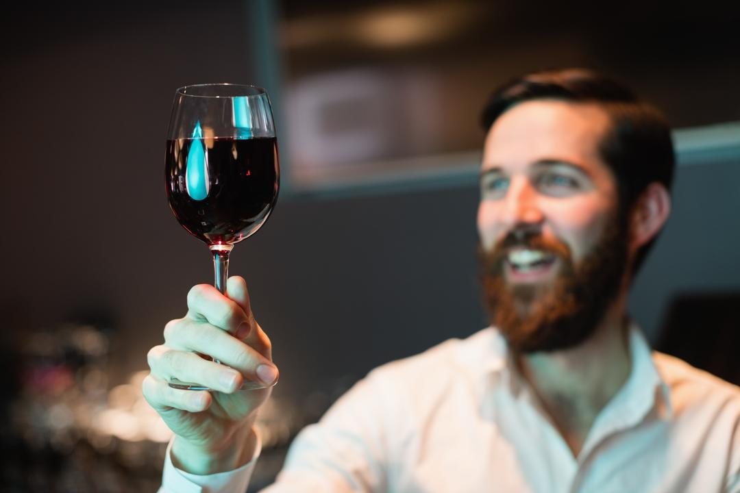 Bartender looking at glass of red wine