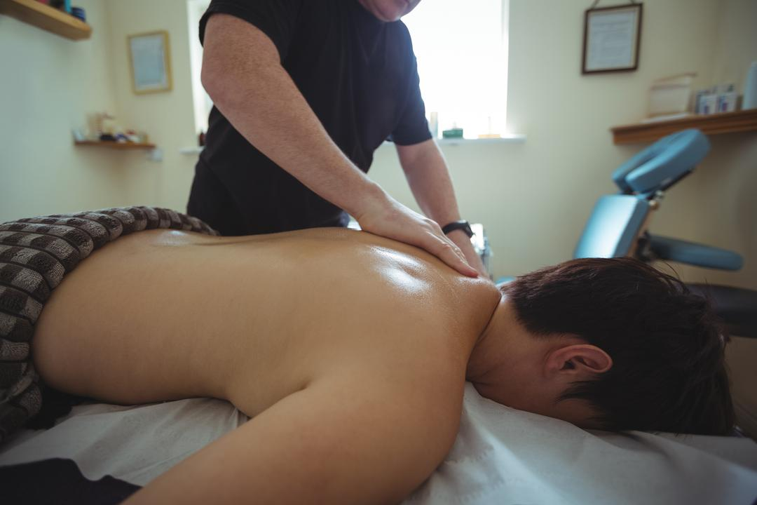 Man receiving shoulder massage from therapist in spa
