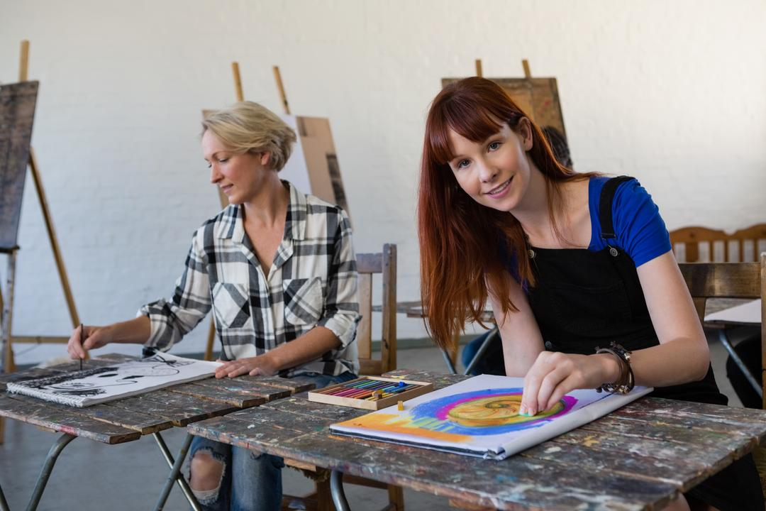 Portrait of adult student drawing on book while sitting by woman in art class Free Stock Images from PikWizard