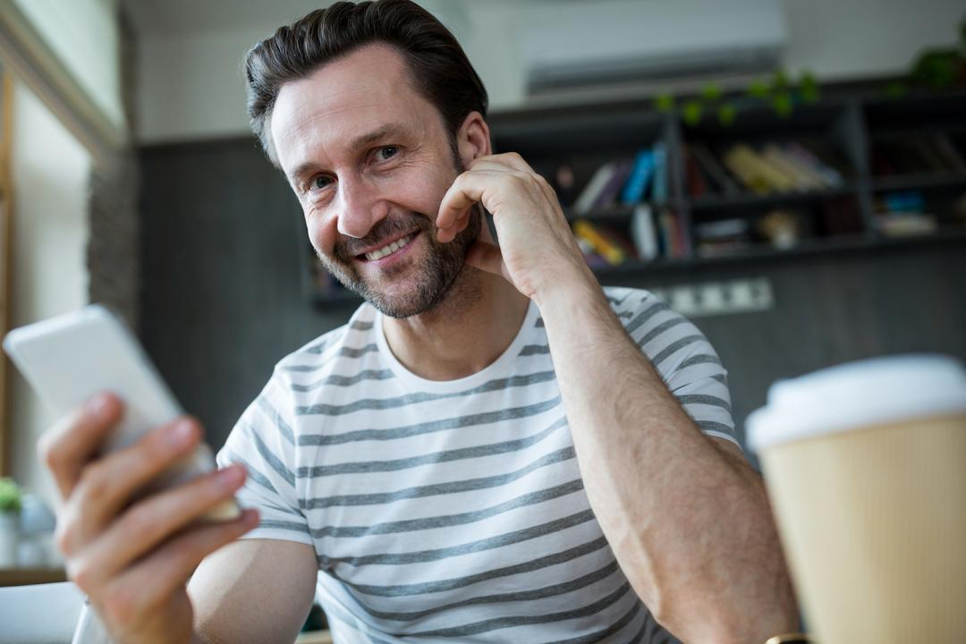 Portrait of smiling man holding his mobile phone in coffee shop