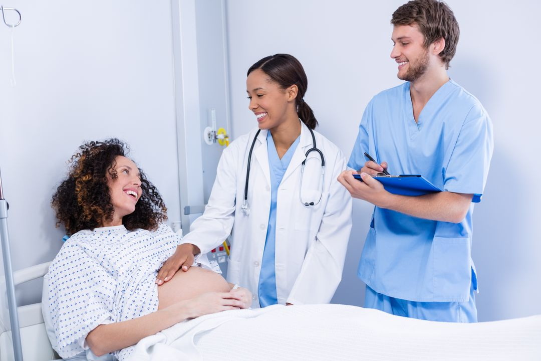 Doctors interacting with pregnant woman in ward of hospital Free Stock Images from PikWizard