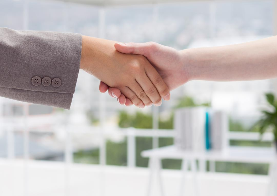 Close up of business executives shaking hands at office workplace