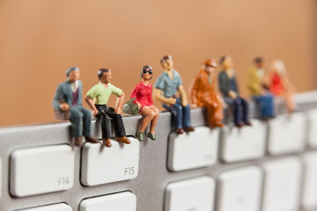Conceptual image of miniature people sitting on top of keyboard Free Stock Images from PikWizard