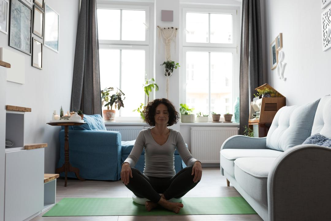 Photo of woman meditating in living room with open windows