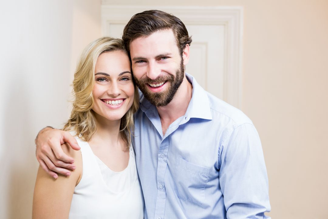 Portrait of happy couple standing with arm around at home Free Stock Images from PikWizard