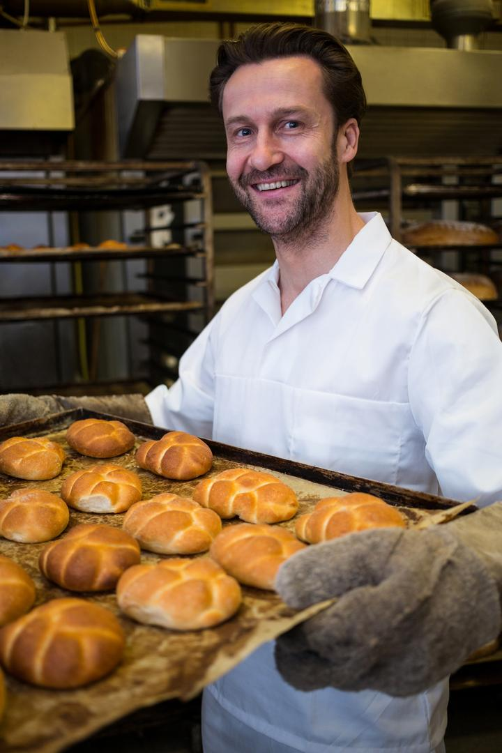 Portrait of smiling baker holding a tray of freshly baked buns