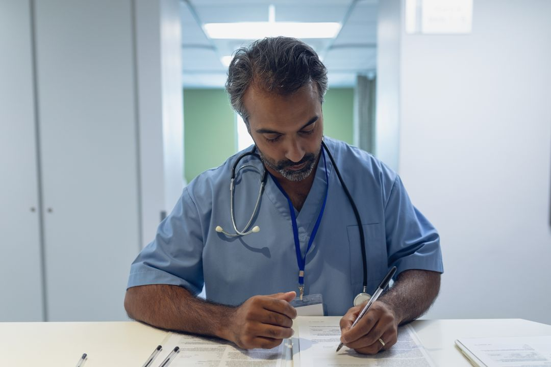 Male doctor reading documents at reception in hospital