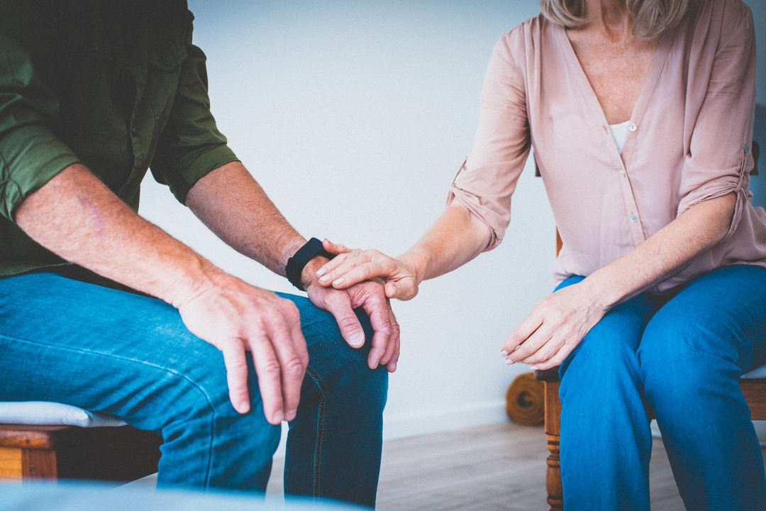 Couple sitting close with hands together