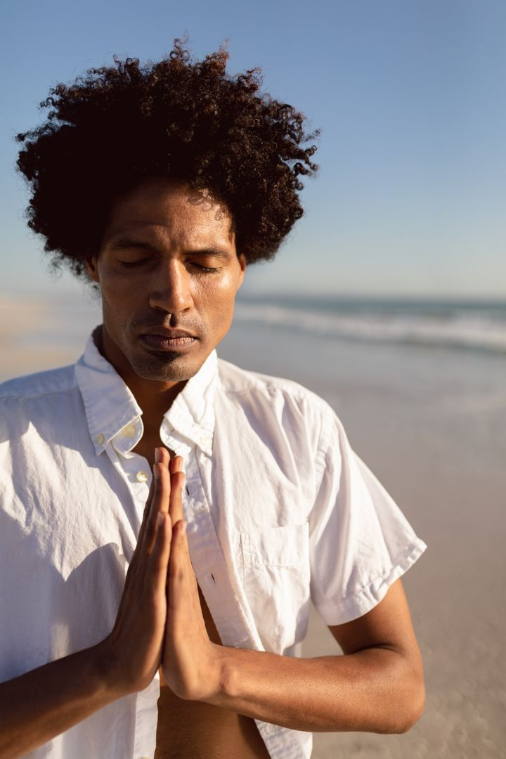 Front view of young African-american man performing yoga on the beach
