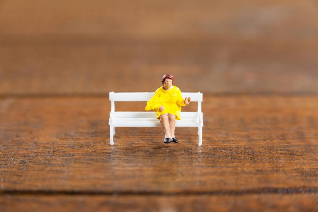 Conceptual image of miniature woman sitting on a bench Free Stock Images from PikWizard