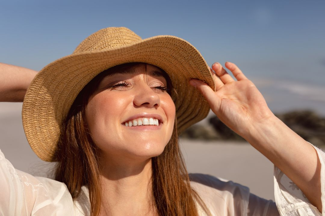 Beautiful young woman in hat looking away on beach in the sunshine